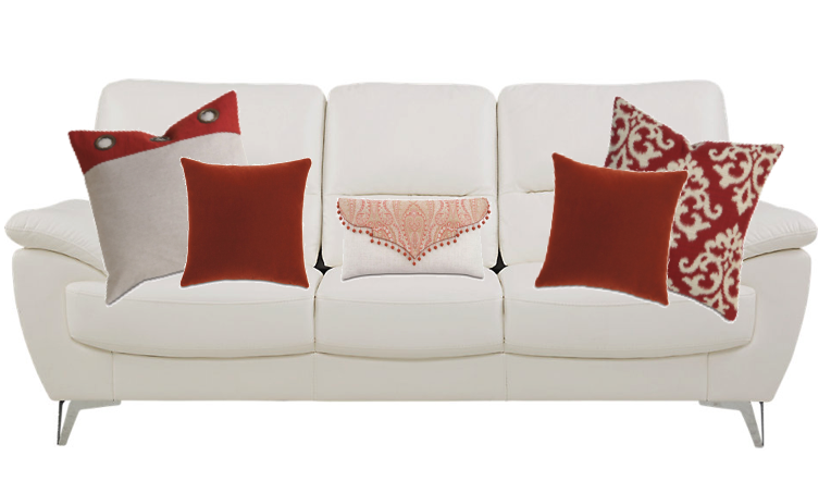 solid white sofa with 5 decorative red pillows of varying prints and sizes