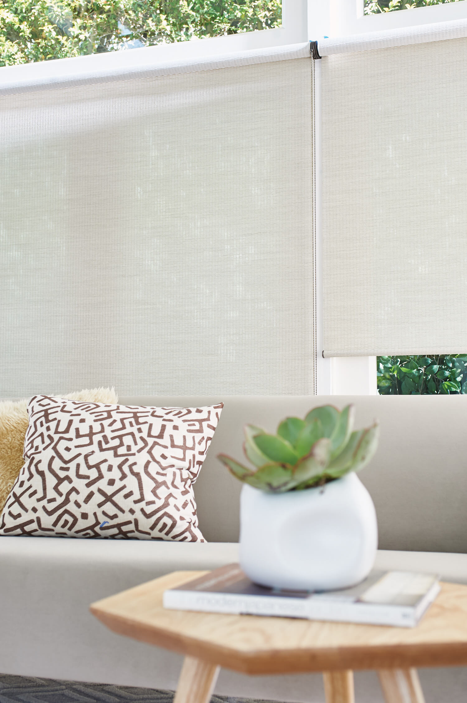 close up of off-white Alustra Woven Textures behind sofa