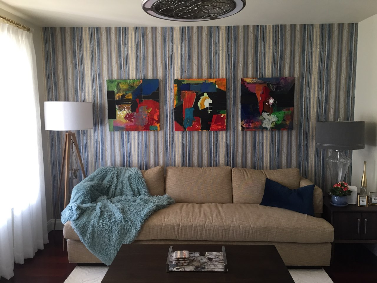 lounge room with blue and tan vertical striped wallpaper on an accent wall