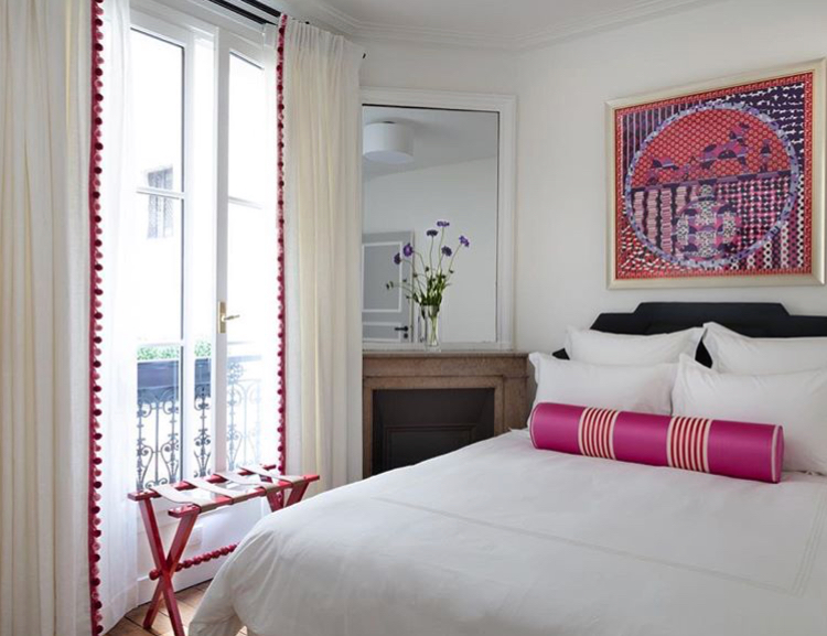 Floor length drapery with bright pink trim in a Paris apartment bedroom