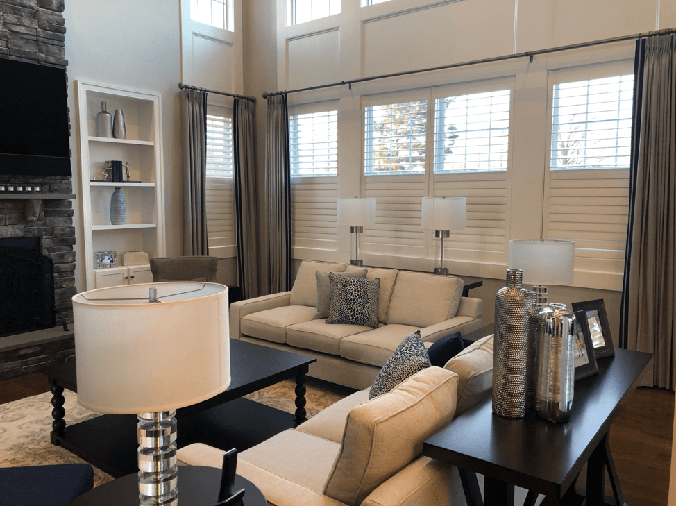 Combining window treatments of Hunter Douglas split tilt plantation shutters with gray drapery panels on 4 side-by-side windows and a single.