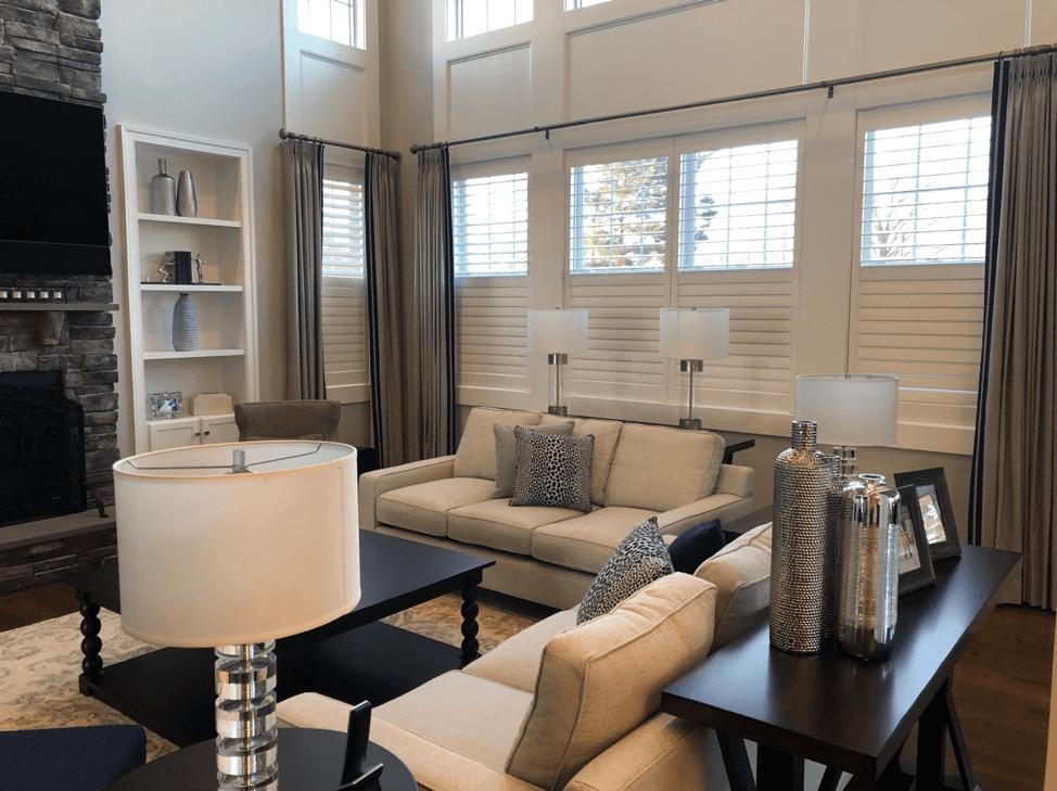 Combining window treatments of Hunter Douglas split tilt plantation shutters with gray drapery panels on 4 side-by-side windows and a single.