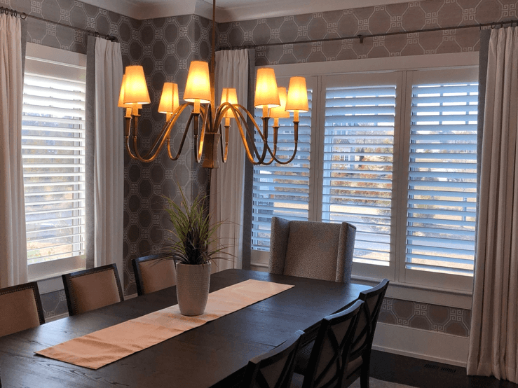 Triple and single dining room windows treated with Hunter Douglas plantation shutters and simple pleated drapery panels.