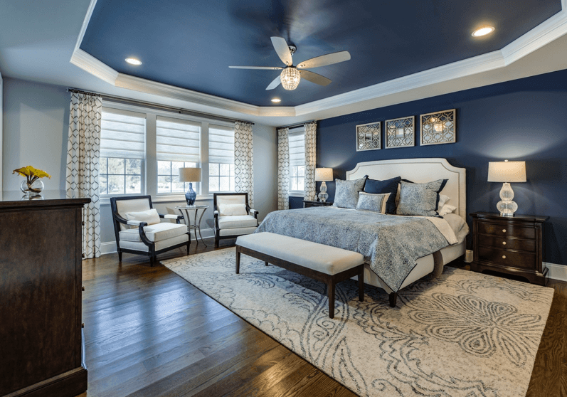 Navy blue and gray master bedroom with Roman shades and drapery panels.