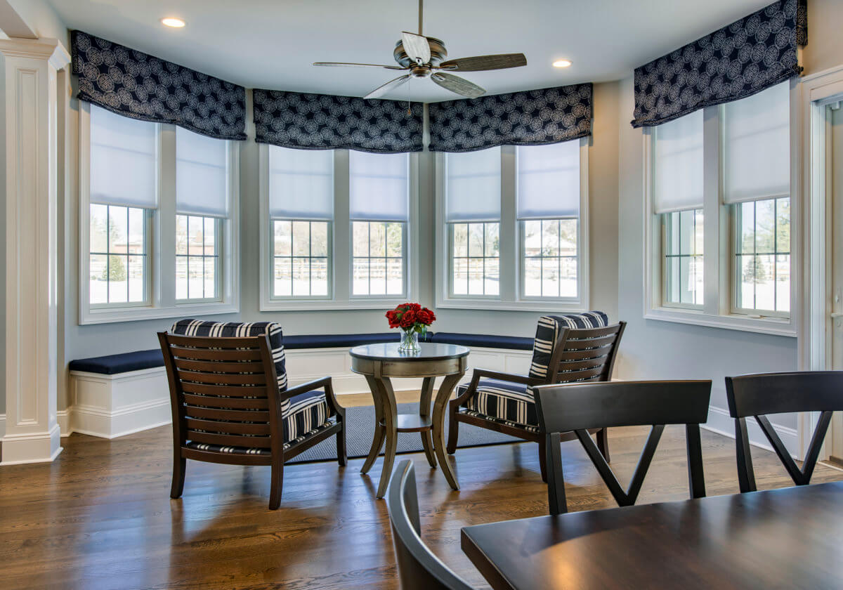 Sunroom nook with 4 sets of side-by-side windows treated with Hunter Douglas Roller shades and valances.
